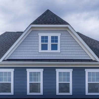 Gable with horizontal vinyl lap siding, double hung window with white frame, shingle facade on a pitched roof attic at an American luxury single family colonial home neighborhood in the USA